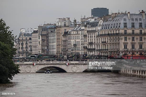 Parisians and tourists cross over the Seine on the Saint Michel bridge while it's underpass has just enough height for a dinghy boat Large sightseing...