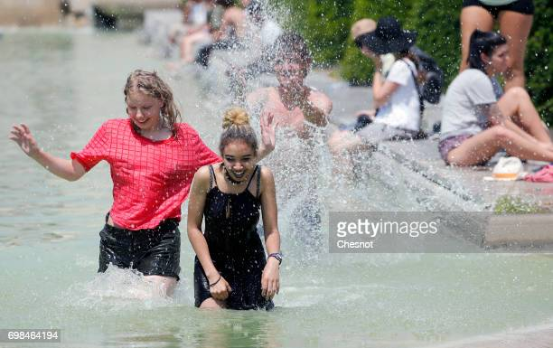 Parisians and tourists enjoy cooling down in the water of the fountain of the Trocadero next to the Eiffel Tower during the heat wave on June 20 2017...