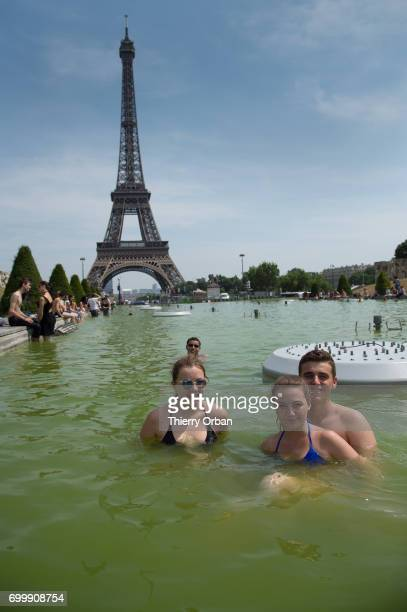 Parisians and tourists enjoy cooling down in the water of the fountain of the Trocadero next to the Eiffel Tower during the heat wave on June 22 2017...