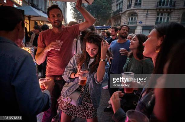Parisians dance in the street and abandon social distancing at a bar in the 2nd Arrondissement as Paris celebrates the first day of summer with Fete...