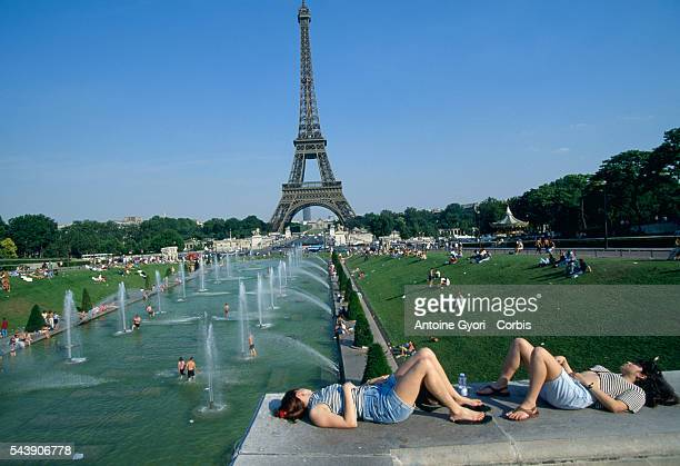 Parisians enjoy resting alongside and swimming in the Trocadero Fountains near the Eiffel Tower during a summer heatwave