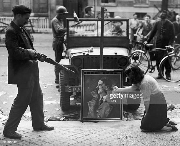 Parisians express their feelings towards a defaced portrait of Nazi leader Adolf Hitler the day after the surrender of the German garrison in the...