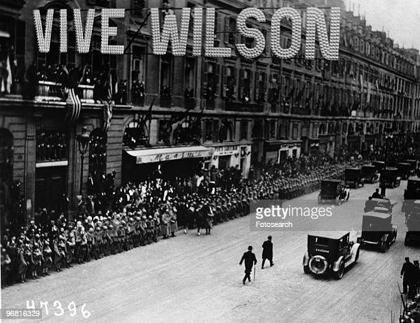 Parisians line the route of American President Woodrow Wilson's motorcade, above the street hangs a 'Vive Wilson' sign, circa 1918. .
