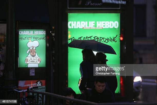 Parisians make their way home past an illuminated advertisement for the latest edition of Charlie Hebdo magazine on January 15 2015 in Paris France...