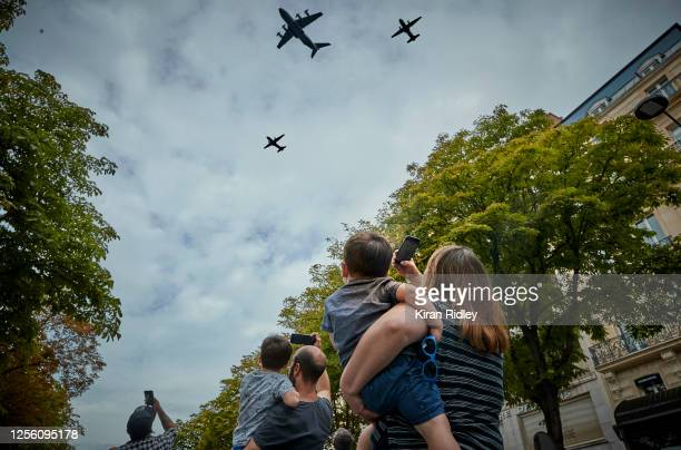 Parisians watch the flypast during the annual Military Parade to celebrate Bastille Day near the Champs Elysees on July 14 2020 in Paris France Due...