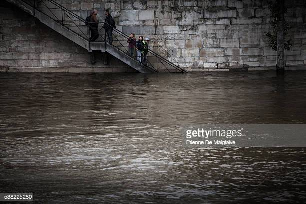 Parisians watch the swollen river Seine from steps as the river's embankments overflow after five days of heavy rain on June 4 2016 in Paris France...