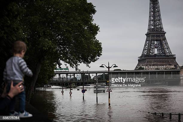 Parisians watch the swollen river Seine near the Eiffel Tower as the river's embankments overflow after five days of heavy rain on June 4 2016 in...