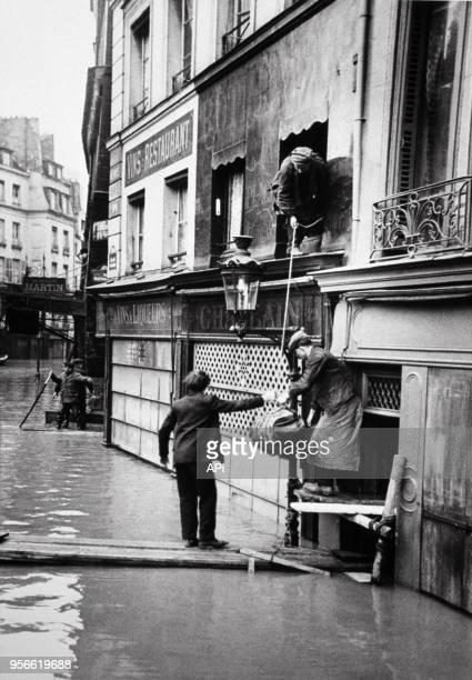 Parisiens évacuant leurs affaires des immeubles inondés par la crue de la Seine en 1910 à Paris France