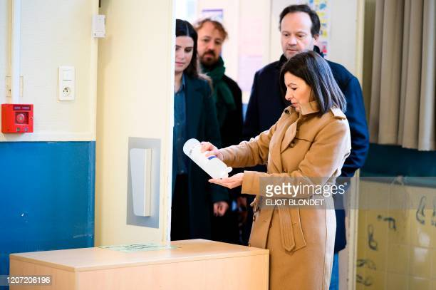 TOPSHOT Paris'incumbent mayor and Socialist party's candidate Anne Hidalgo uses hand sanitizer before voting during the first round of the French...