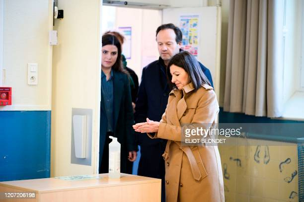 Paris'incumbent mayor and Socialist party's candidate Anne Hidalgo uses hand sanitizer before voting during the first round of the French municipal...