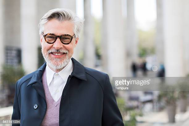 parissien man smiling at camera on paris streets - 50 59 years stock pictures, royalty-free photos & images