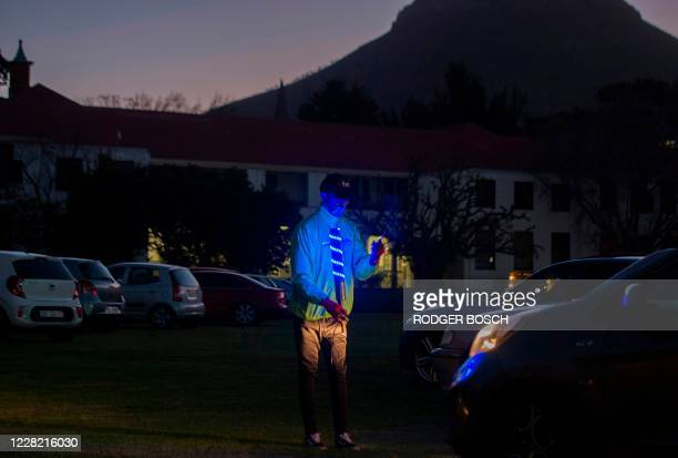 A park attendant helps people to park their cars in the right position at the Galileo drivein being held on a school sports field in Cape Town with...