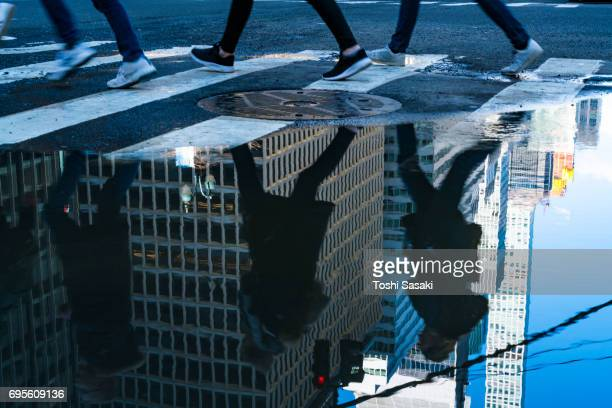 park avenue architectures and pedestrians silhouettes reflect to the puddle on the road at midtown manhattan new york city. - パークアベニュー ストックフォトと画像