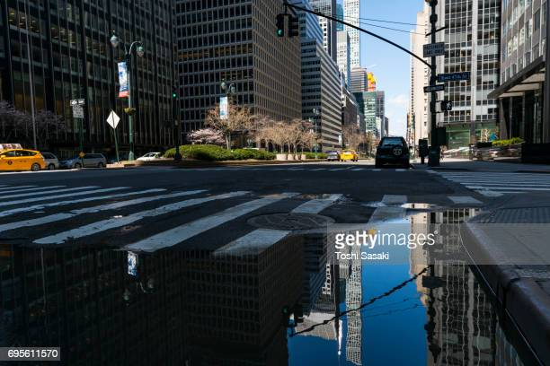 park avenue architectures reflect to the puddle on the road at midtown manhattan new york city. - パークアベニュー ストックフォトと画像