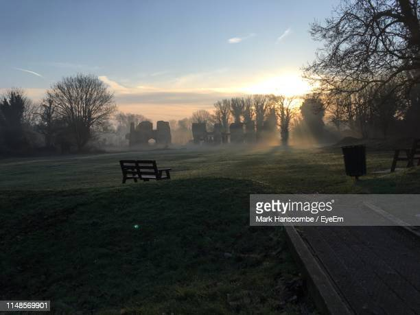 park bench on field against sky during sunset - st. albans stock pictures, royalty-free photos & images