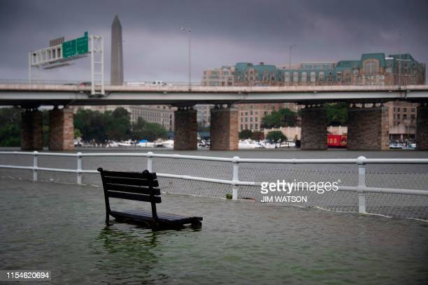 TOPSHOT A park bench sits under water in East Potomac Park in Washington DC on July 8 after a storm caused flooding