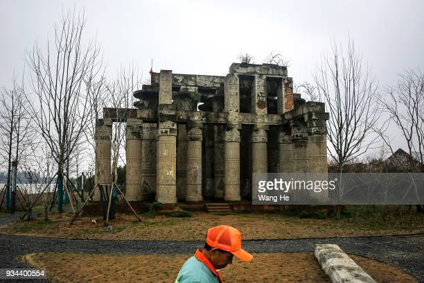 A park cleaner walks in front of a replica of Karnak Temple in Egypt at the abandoned Wanguo Park on March 19 2018 in Wuhan Hubei province The park...