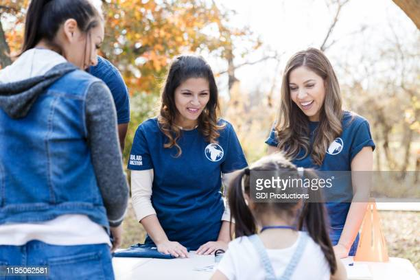 park cleanup volunteers smile and encourage unrecognizable girl - selfless stock pictures, royalty-free photos & images
