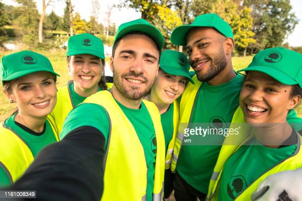 park clean-up volunteers taking a selfie - environmentalist stock pictures, royalty-free photos & images