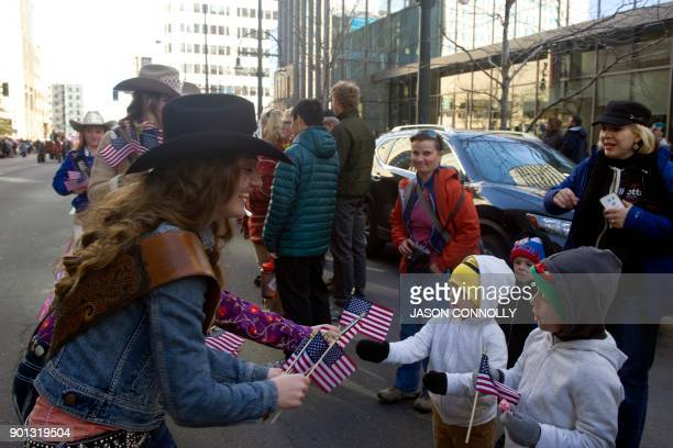 Park County Fair Rodeo Queen Abby Schmidt of Bailey Colorado hands out US flags to children during the National Western Stock Show KickOff Parade in...