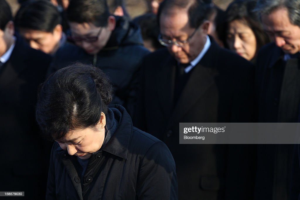 Park Geun Hye, South Korea's president-elect, front, observes a minute of silence on her visit to the National Cemetery in Seoul, South Korea, on Thursday, Dec. 20, 2012. Park, 60, of the ruling New Frontier Party, defeated main opposition nominee Moon Jae In, 51.6 percent to 48 percent, the biggest margin of victory in 25 years. Photographer: SeongJoon Cho/Bloomberg via Getty Images