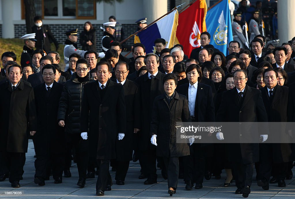 Park Geun Hye, South Korea's president-elect, front row second from right, visits the National Cemetery in Seoul, South Korea, on Thursday, Dec. 20, 2012. Park, 60, of the ruling New Frontier Party, defeated main opposition nominee Moon Jae In, 51.6 percent to 48 percent, the biggest margin of victory in 25 years. Photographer: SeongJoon Cho/Bloomberg via Getty Images