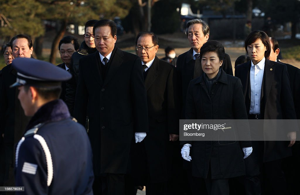 Park Geun Hye, South Korea's president-elect, second right, visits the National Cemetery in Seoul, South Korea, on Thursday, Dec. 20, 2012. Park, 60, of the ruling New Frontier Party, defeated main opposition nominee Moon Jae In, 51.6 percent to 48 percent, the biggest margin of victory in 25 years. Photographer: SeongJoon Cho/Bloomberg via Getty Images