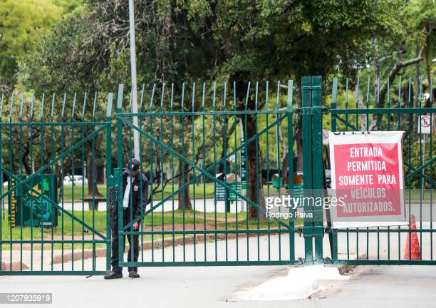 A park guard closing the gates of Ibirapuera Park during a lockdown aimed at stopping the spread of the coronavirus pandemic on March 21 in Sao Paulo...