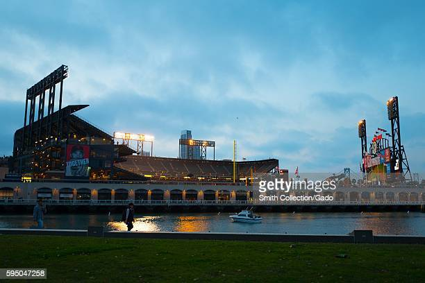 ATT Park home of the San Francisco Giants baseball team illuminated at night after a home game viewed from China Basin Park across McCovey Cove San...