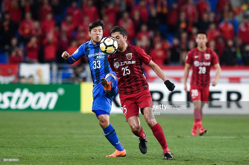 Park Joo-Ho #33 of Ulsan Hyundai and Odil Ahmedov #25 of Shanghai SIPG compete for the ball during the 2018 AFC Champions League Group F match between Ulsan Hyundai FC and Shanghai SIPG at the Ulsan Munsu Football Stadium on March 13, 2018 in Ulsan, South Korea.