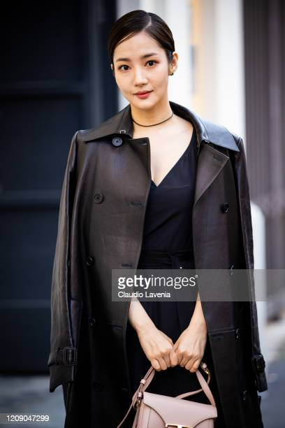 Park Min-young, wearing a black dress, black leather coat and nude Tod's bag, is seen outside Tod's show, during Milan Fashion Week Fall/Winter...