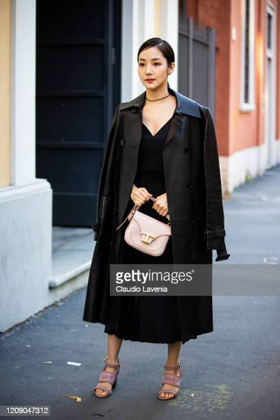 Park Min-young, wearing a black dress, black leather coat, pink sandals and nude Tod's bag, is seen outside Tod's show, during Milan Fashion Week...
