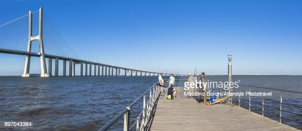 Park of the Nations, fishermen on a dock and Vasco da Gama Bridge on the background