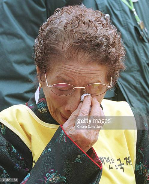 Park OkRyun a former World War II South Korean comfort woman wipes a tear from her eye as she attends a protest in front of the Japanese Embassy...