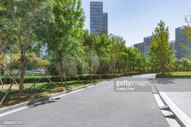 park pedestrian walkway toward modern skyscrapers - park stock-fotos und bilder