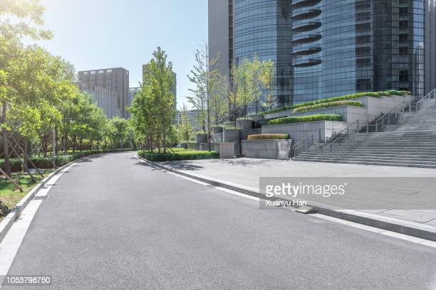 park pedestrian walkway toward modern skyscrapers - business community stock pictures, royalty-free photos & images