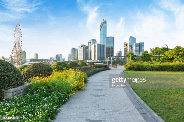 park pedestrian walkway toward modern skyscrapers - suzhou stock pictures, royalty-free photos & images