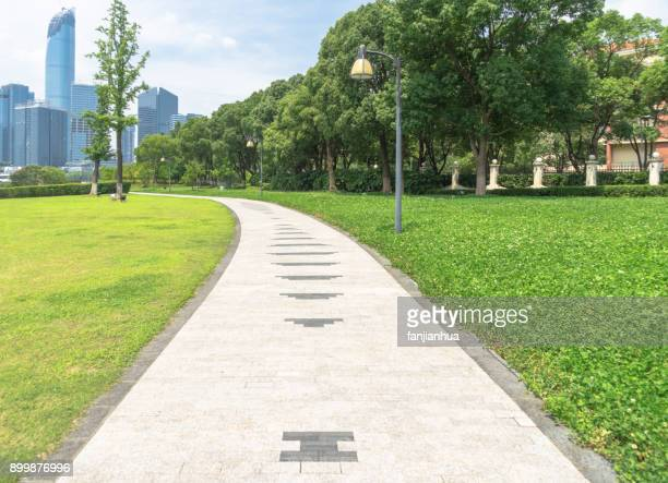 park pedestrian walkway toward modern skyscrapers - public park stock photos and pictures
