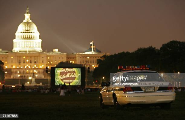 S Park Police officer is parked near people watching an openair movie near the US Capitol along the National Mall July 17 2006 in Washington DC In...