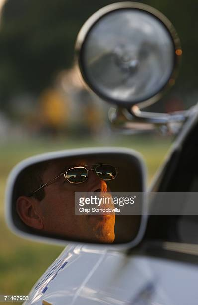 S Park Police officer sits in his cruiser near a group of people playing kickball along the National Mall at dusk July 17 2006 in Washington DC In...