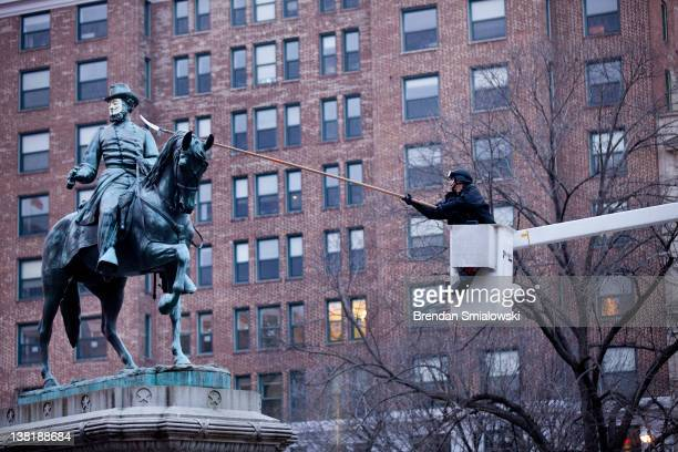 Park Police officer uses a limb saw to remove a mask of Guy Fawkes from a statue of James McPherson in McPherson Square February 4 2012 in Washington...