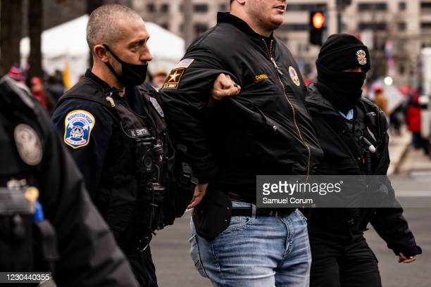Park Police officers arrest a man on gun charges after officers spotted him carrying a concealed firearm during a pro-Trump rally at Freedom Plaza on...