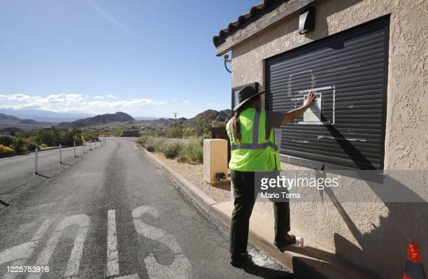 Park ranger affixes an information sign to an unstaffed entrance station in Joshua Tree National Park one day after the park reopened after being...
