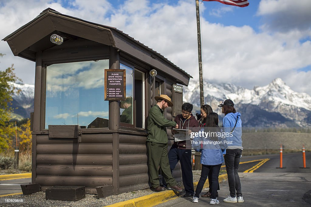 Park ranger Dustin Eads explained to a group of tourists from China who planed their vacation 6 months in advance where they were and were not allowed to go as he turns away visitors from entering the Grand Teton National Park south entrance at Grand Teton National Park in Moose, DC on Tuesday October 1, 2013.