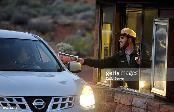 Park ranger Lee Wilson passes out park information to visitors at the entrance to Zion National Park on October 12 2013 in Springdale Utah The Obama...