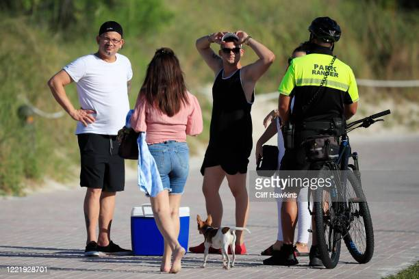 Park ranger speaks to visitors in South Pointe Park on April 29 2020 in Miami Beach Florida The city of Miami Beach partially reopened parks and...
