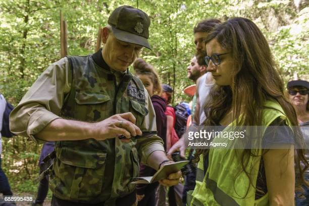 Park ranger takes a photo of an ID of a protester during a protest against the large scale logging at Bialowieza forest, an Unesco natural world...