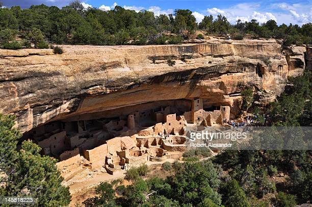 Park ranger talks with a group of visitors at Cliff Palace ruins in Mesa Verde National Park in Colorado. The park's stone and adobe cliff dwellings...