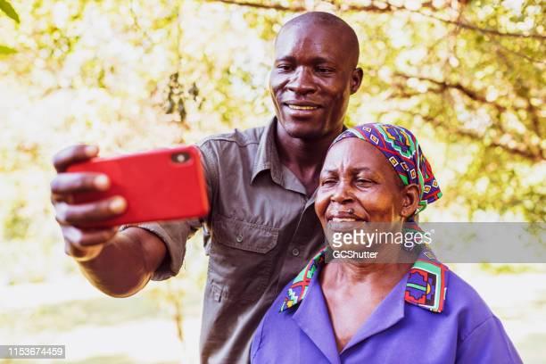彼の母親はスマートフォンを使用して自分撮りを取ると公園のレンジャー - ザンビア ストックフォトと画像