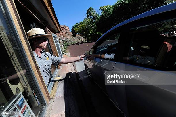 Park ranger Zac O'Neal collects park fees from visitors on his first day back to work at the entrance to Zion National Park on October 12 2013 in...